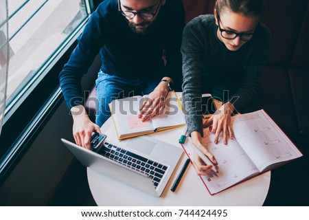 Cropped image of male and female employees team working on business startup project and writing down general information to notepad.Young freelancers planning schedule using marker and textbook