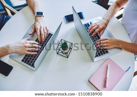 Photo of Cropped image of male and female hands typing text article for posting content on website using free wireless 4g internet in coworking space, it professionals updating software on laptop computers