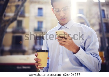 Photo of Cropped image of male blogger writing new travel story on own internet website and reading coments walking outdoors and recreating during free time holding coffee cup with mock ip for brand name