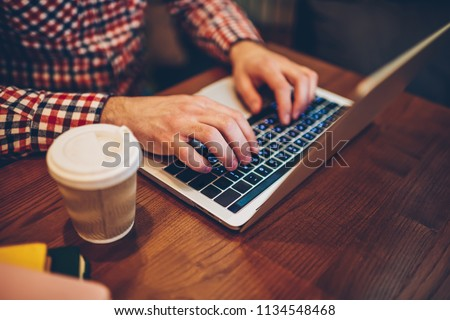 Photo of Cropped image of male hands typing information for website via keyboard on laptop computer connected to free wireless internet in coffee shop, it professional working remotely with modern netbook