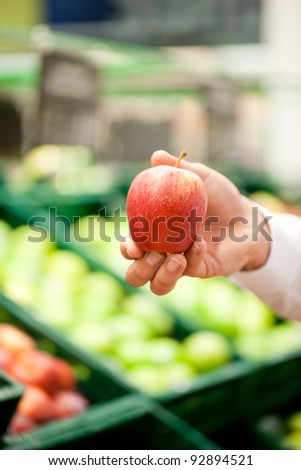Cropped image of male's hand holding an apple at supermarket