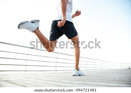 Cropped image of man athlete runner's feet and shoes running along beach pier #494721481