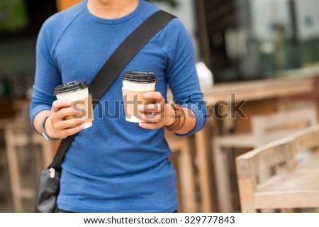Cropped image of man holding two cups of take-out coffee