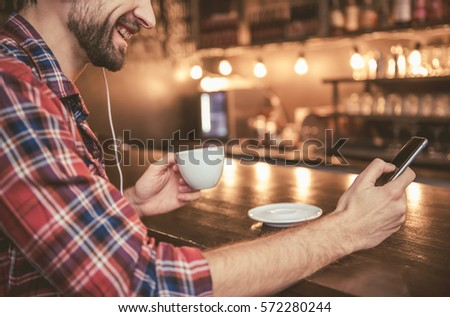 Cropped image of man in headphones listening to music using a smartphone, drinking coffee and smiling while resting in cafe #572280244