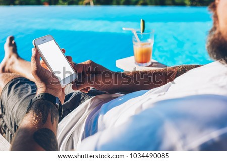 Cropped image of man lying near swimming pool with cocktail and chatting online via high speed internet connected to modern smartphone.Male installing app on mobile phone enjoying summer vacations