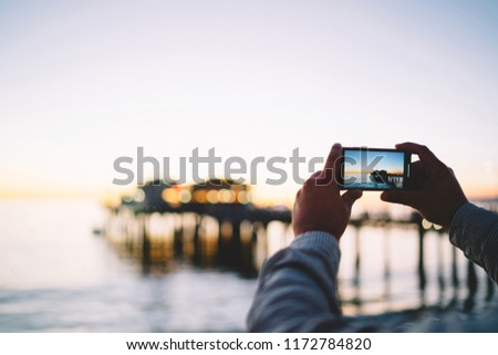 Cropped image of man make picture of beautiful environment and sea at evening having good app on mobile phone,male taking image of ocean in twilight via modern smartphone and camera for photo in dark
