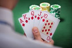 Cropped image of man playing winning hand of poker
