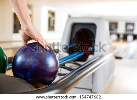 Cropped image of man's hand picking up bowling ball from rack in club