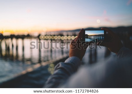 Cropped image of man taking photo in evening dusk of nature environment using modern smartphone camera, back view of hipster guy holding mobile phone making picture of sea water via app in twilight