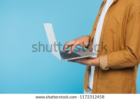 cropped image of man using laptop isolated on blue
