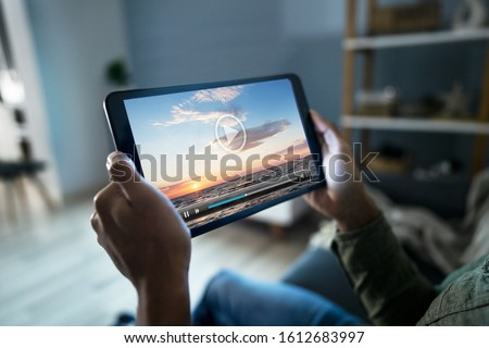 Cropped Image Of Man Watching Movie On Digital Tablet At Home
