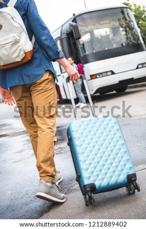 cropped image of man with backpack carrying wheeled bag near travel bus at street #1212889402