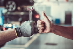 Cropped image of mechanics working in auto service. One is holding a spanner while the other is showing Ok sign