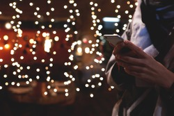 Cropped image of person booking hotel via smart phone application during vacation holidays in Christmas. Closely of a hipster girl is using her cell telephone, while is standing outdoors in night time