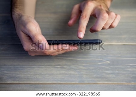 Cropped image of person holding and using smart phone at desk #322198565