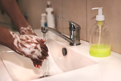 Cropped image of person washing hands at sink in bathroom, Coronavirus hand washing for clean hands hygiene Covid-19 spread prevention viral, bacterial infections. African-American woman washes hands.