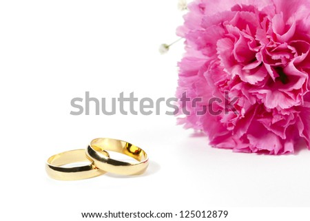 Cropped image of pink carnation with two wedding ring lying on a white background