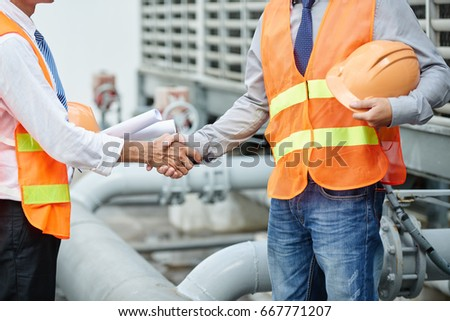 Cropped image of plant engineers in orange vests shaking hands #667771207