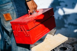 Cropped image of red toolbox in a man hand whle holding after finish his work.