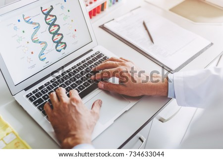 Cropped image of senior experienced scientist is working in laboratory. Doing investigations using laptop