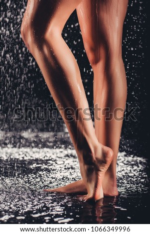Cropped image of sexy woman in shower. Attractive young naked woman under water drops isolated on black background. Close-up of woman's legs.