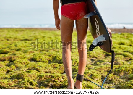 Cropped image of slim female surfer with nice buttocks, slender legs, wears red bikini, carries surfboard, fastened by leash, stands on beach covered with green vegetation, has sand on body.