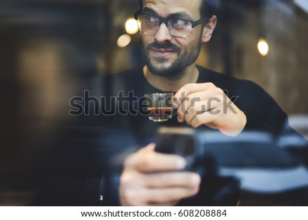 Cropped image of smart handsome businessman with stylish spectacles holding digital tablet and glass with coffe in hand. Close up young man using modern device and using free internet connection #608208884