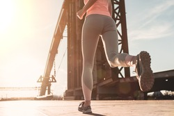 Cropped image of sporty girl is running on street during the sunset. Jogging.