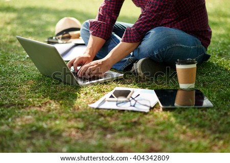 Cropped image of student sitting on the ground and working on laptop