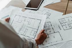 Cropped image of the building plan on the paper on the mess wooden table in the interior designer's hands.