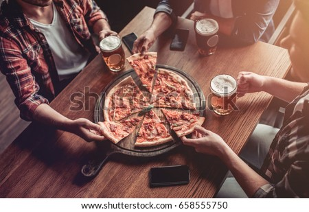 Cropped image of three male friends in bar are drinking beer and eating pizza with smartphone on the table. stock photo