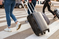 Cropped image of three women from back walking across pedestrian crossing and carrying luggage to airport. Air travel or holiday concept