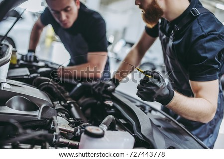 Cropped image of two handsome mechanics in uniform are working in auto service. Car repair and maintenance. Checking the oil level.