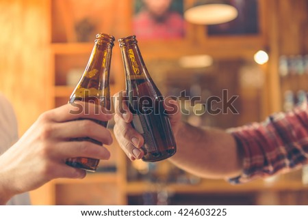 Cropped image of two men clanging bottles of beer together while sitting at bar counter in a modern urban cafe #424603225
