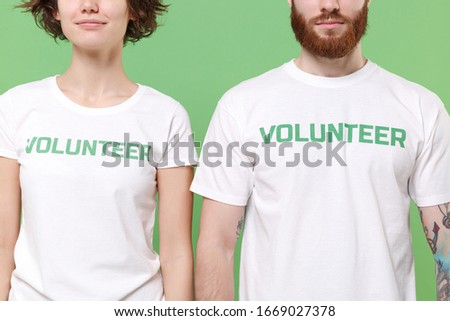 Photo of Cropped image of two young friends couple in white volunteer t-shirt isolated on pastel green wall background, studio portrait. Voluntary free work assistance help charity grace teamwork concept