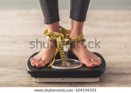 Cropped image of woman feet standing on weigh scales, on gray background. Legs winded with a tape measure