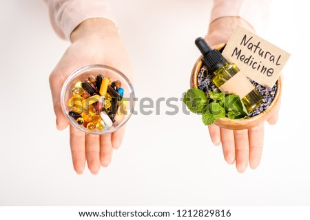 cropped image of woman holding bowls with natural medicine oil and pharmacological pills isolated on white