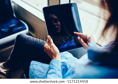 Photo of Cropped image of woman holding digital tablet for watching video and online content while sitting in bus, female using portable oc and free wifi connection in public transport read electronic book