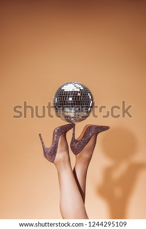 cropped image of woman holding shiny disco ball on high heels at party on beige #1244295109