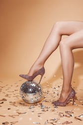 cropped image of woman in high heels putting leg on disco ball, beige floor with confetti