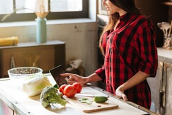 Cropped image of woman in red shirt standing in kitchen with tablet computer and looking recipes. Side view