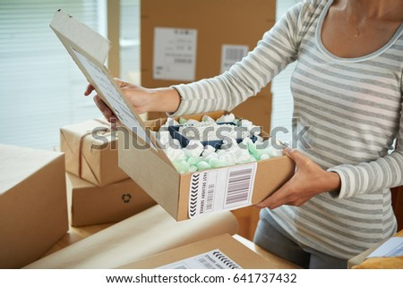 Cropped image of woman opening parcel with pearl necklace inside