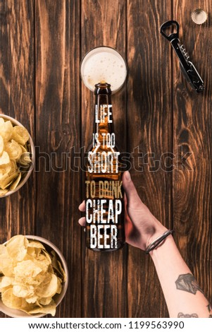 """cropped image of woman pouring beer into glass at wooden table with crispy chips, with """"life is too short to drink cheap beer"""" inspiration"""