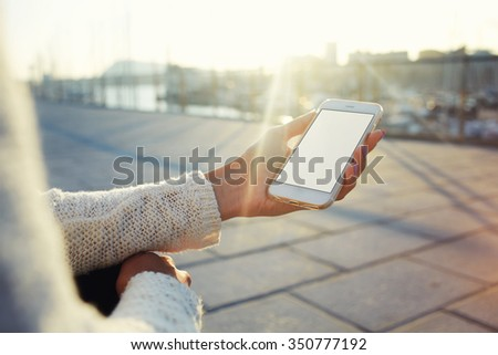 Cropped image of woman\'s hands holding cell telephone with blank copy space screen for your text message or promotional content, hipster girl using mobile phone while resting outdoors during free time