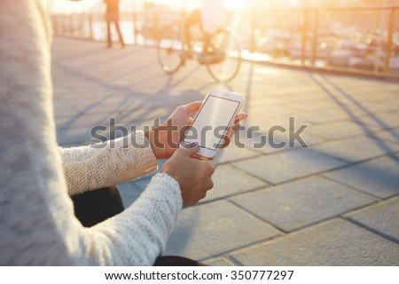 Cropped image of woman\'s hands holding smart phone with blank copy space screen for your text message or promotional content, female chatting in network on cell telephone while sitting near sea port