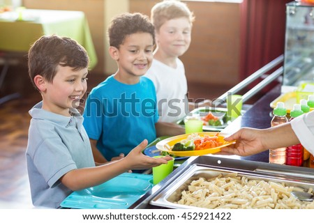 Cropped image of woman serving food to schoolchildren in canteen Photo stock ©