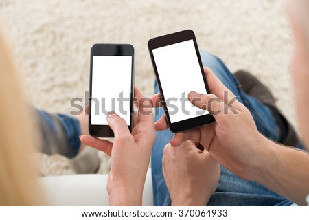 Cropped image of young couple using smart phones with blank screens at home #370064933