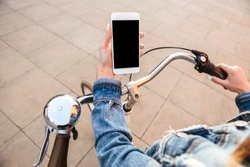 Cropped image of young lady outdoors on bicycle on the street using mobile phone. Empty black display.
