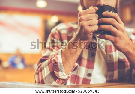 Cropped image of young modern businessman with beard in casual clothes drinking coffee while sitting in a cafe #529069543