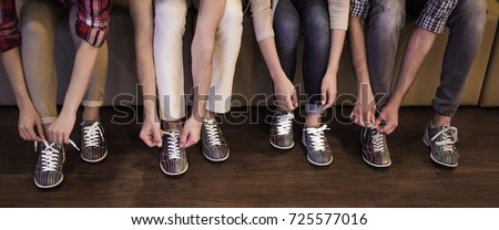 Cropped image of young people lacing up bowling shoes ready to play bowling